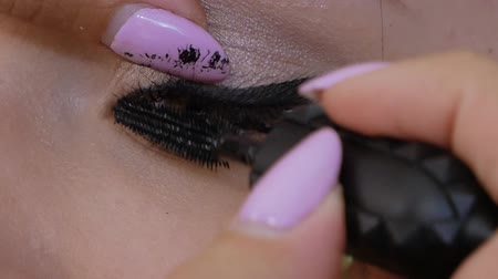 contorno : Beautiful woman uses mascara to make eyelashes green-brown eyes. Slowmotion of makeup artist professionally applying mascara to client