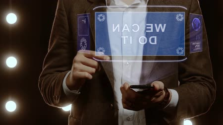 frase : Businessman activates conceptual HUD hologram on smartphone with text We can do it. Man in a white shirt and jacket with a holographic screen on the background of lights