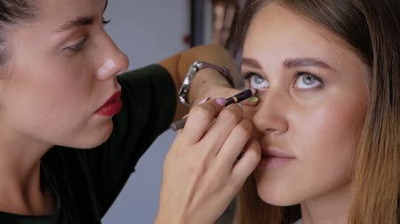 frustata : Slow motion in a beauty salon. Professional makeup artist makes eyeliner with a pencil on the lower eyelid of a beautiful girl. Woman client in a beauty salon does makeup