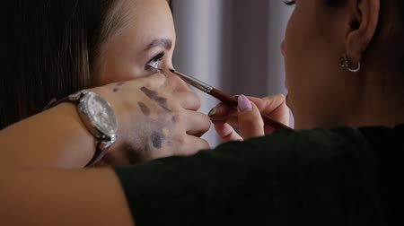obrys : Slow motion in a beauty salon. Professional makeup artist makes eyeliner with a brush on the lower eyelid of a beautiful girl. Woman client in a beauty salon does makeup