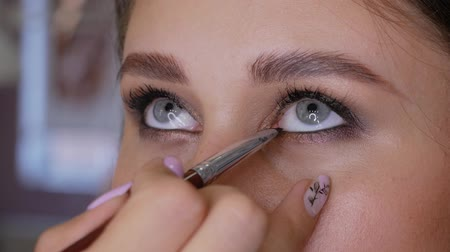 frustata : Hand of professional makeup artist makes eyeliner with a brush on the lower eyelid of a beautiful girl. Woman client in a beauty salon does makeup Filmati Stock