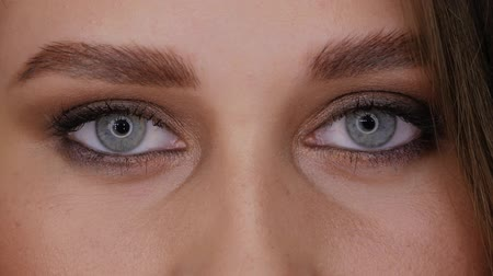 стегать : Eyes of young woman with professional ringlight makeup looks straight into the frame and closes her eyes slow motion. Beautiful girl with blue eyes close-up circular light