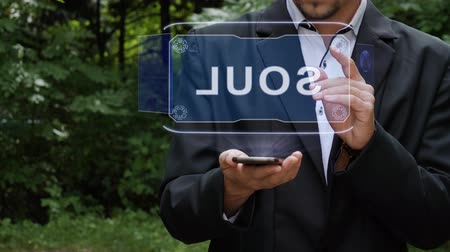 ziel : Unrecognizable businessman activates conceptual HUD holograms on smartphone with text Soul. Bearded man in a white shirt and a jacket with a holographic screen on a background of green trees