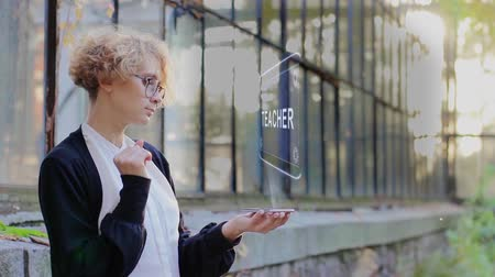 talent : Curly young woman in glasses interacts with a hud hologram with text Teacher. Blonde girl in white and black clothes uses technology of the future mobile screen