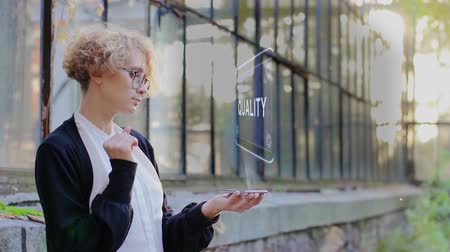 Curly young woman in glasses interacts with a hud hologram with text Quality. Blonde girl in white and black clothes uses technology of the future mobile screen