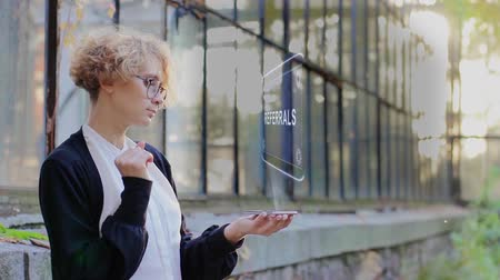 referred : Curly young woman in glasses interacts with a hud hologram with text Referrals. Blonde girl in white and black clothes uses technology of the future mobile screen