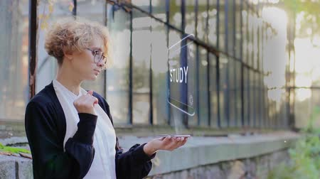 lesson : Curly young woman in glasses interacts with a hud hologram with text Study. Blonde girl in white and black clothes uses technology of the future mobile screen
