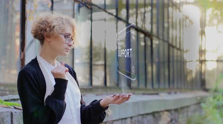 Curly young woman in glasses interacts with a hud hologram with text Support. Blonde girl in white and black clothes uses technology of the future mobile screen