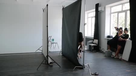 professional photography : Studio photography. Female photographer in a black dress works with a model in a photo studio