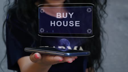 mülkiyet : Unrecognizable curly brunette woman showing HUD hologram with text Buy house. Girl uses technology of the future on a mobile screen