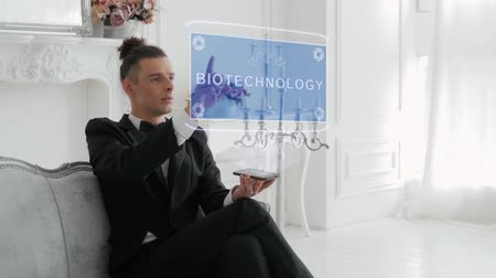 nanotechnologia : Guy businessman activates conceptual HUD hologram on smartphone with text Biotechnology. Young man in a white shirt and a jacket with a holographic screen on a background of the luxury room