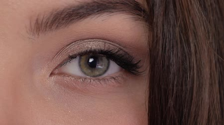 bizakodó : Young woman looks straight into the frame and closes her eye slow motion. Beautiful girl with green brown eye close-up