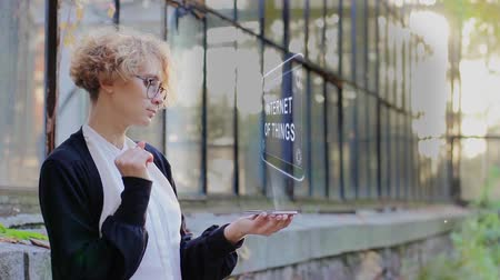 senzor : Curly young woman in glasses interacts with a hud hologram with text Internet of things. Blonde girl in white and black clothes uses technology of the future mobile screen