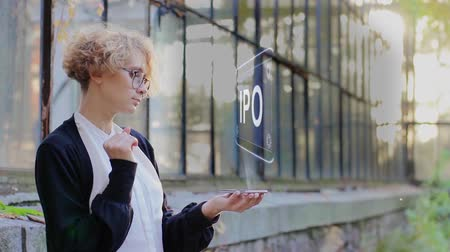 initial : Curly young woman in glasses interacts with a hud hologram with text IPO. Blonde girl in white and black clothes uses technology of the future mobile screen