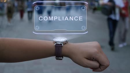 megfelel : Female hand with futuristic smartwatch shows HUD hologram with text Compliance. Woman uses holographic technology of future on wristwatch against background of evening city with people
