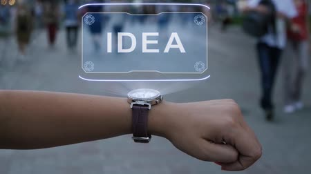 uitvinding : Female hand with futuristic smartwatch shows HUD hologram with text Idea. Woman uses holographic technology of future on wristwatch against background of evening city with people