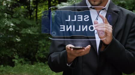 digital code : Unrecognizable businessman activates conceptual HUD holograms on smartphone with text Sell online. Bearded man in a white shirt and a jacket with a holographic screen on a background of green trees Stock Footage