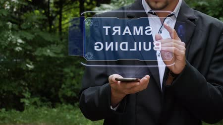 Unrecognizable businessman activates conceptual HUD holograms on smartphone with text Smart building. Bearded man in a white shirt and a jacket with a holographic screen on a background of green trees