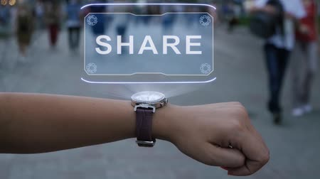 przyszłość : Female hand with futuristic smartwatch shows HUD hologram with text Share. Woman uses holographic technology of future on wristwatch against background of evening city with people