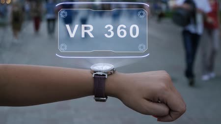 konzol : Female hand with futuristic smartwatch shows HUD hologram with text VR 360. Woman uses holographic technology of future on wristwatch against background of evening city with people