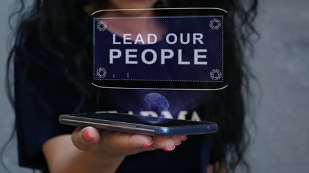 Unrecognizable curly brunette woman showing HUD hologram with text Lead our people. Girl uses technology of the future on a mobile screen