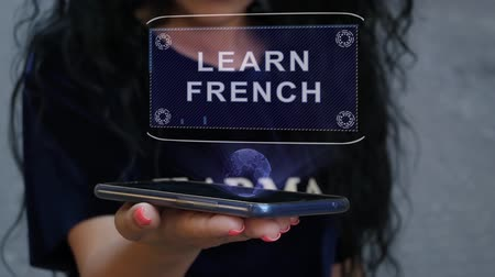 advice : Unrecognizable curly brunette woman showing HUD hologram with text Learn French. Girl uses technology of the future on a mobile screen