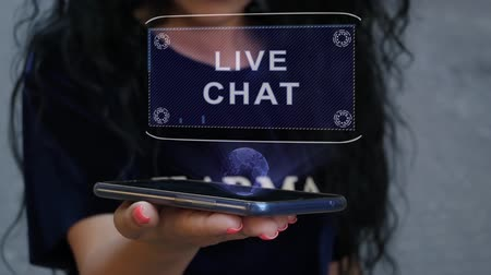 Unrecognizable curly brunette woman showing HUD hologram with text Live chat. Girl uses technology of the future on a mobile screen Dostupné videozáznamy