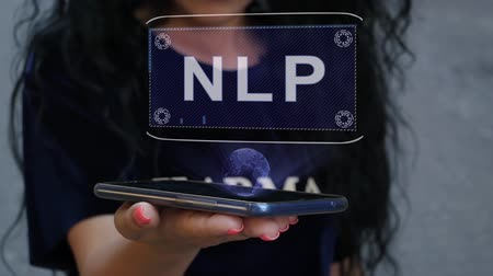 neuro : Unrecognizable curly brunette woman showing HUD hologram with text NLP. Girl uses technology of the future on a mobile screen