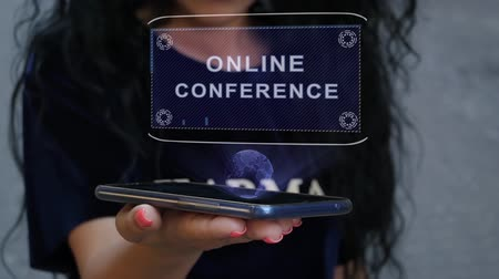 образовательный : Unrecognizable curly brunette woman showing HUD hologram with text Online conference. Girl uses technology of the future on a mobile screen Стоковые видеозаписи