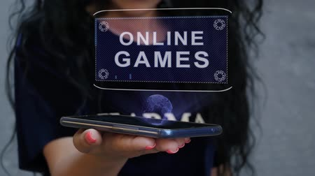 Unrecognizable curly brunette woman showing HUD hologram with text Online Games. Girl uses technology of the future on a mobile screen Stockvideo