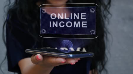 investidor : Unrecognizable curly brunette woman showing HUD hologram with text Online income. Girl uses technology of the future on a mobile screen