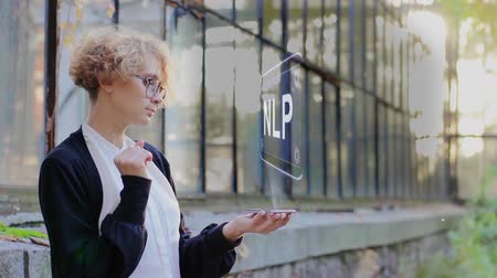 neuro : Curly young woman in glasses interacts with a hud hologram with text NLP. Blonde girl in white and black clothes uses technology of the future mobile screen