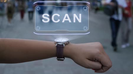 requisito : Female hand with futuristic smartwatch shows HUD hologram with text Scan. Woman uses holographic technology of future on wristwatch against background of evening city with people