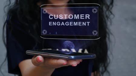 подтверждать : Unrecognizable curly brunette woman showing HUD hologram with text Customer engagement. Girl uses technology of the future on a mobile screen
