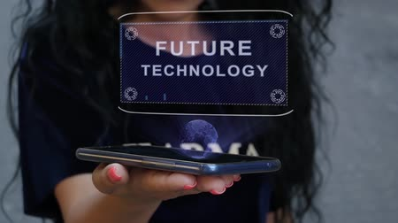 visão global : Unrecognizable curly brunette woman showing HUD hologram with text Future technology. Girl uses technology of the future on a mobile screen