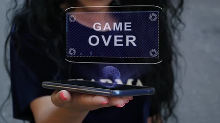 orthographe : Unrecognizable curly brunette woman showing HUD hologram with text Game Over. Girl uses technology of the future on a mobile screen