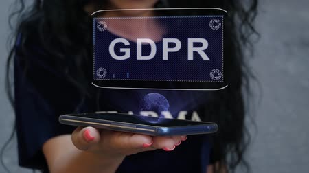 gdpr : Unrecognizable curly brunette woman showing HUD hologram with text GDPR. Girl uses technology of the future on a mobile screen Stock Footage