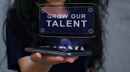 insight : Unrecognizable curly brunette woman showing HUD hologram with text Grow our talent. Girl uses technology of the future on a mobile screen Stock Footage