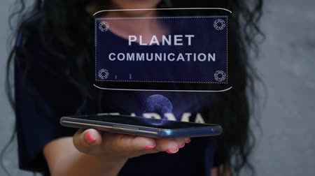 wi fi : Unrecognizable curly brunette woman showing HUD hologram with text Planet communication. Girl uses technology of the future on a mobile screen
