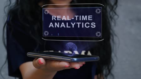 índice : Unrecognizable curly brunette woman showing HUD hologram with text Real-time analytics. Girl uses technology of the future on a mobile screen