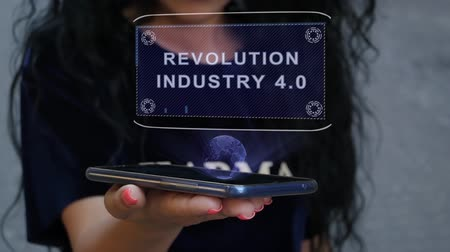 čtvrtý : Unrecognizable curly brunette woman showing HUD hologram with text Revolution Industry 4.0. Girl uses technology of the future on a mobile screen Dostupné videozáznamy