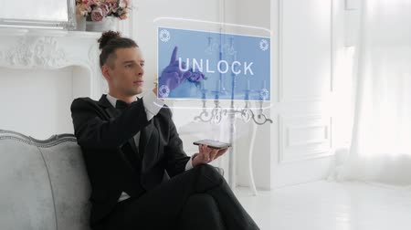 identificar : Guy businessman activates conceptual HUD hologram on smartphone with text Unlock. Young man in a white shirt and a jacket with a holographic screen on a background of the luxury room