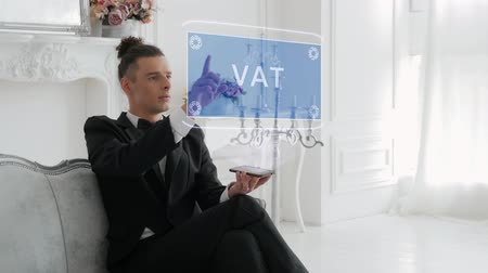 стратегический : Guy businessman activates conceptual HUD hologram on smartphone with text VAT. Young man in a white shirt and a jacket with a holographic screen on a background of the luxury room