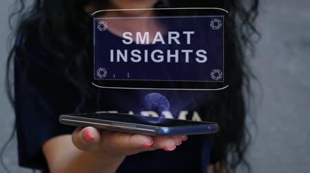 insight : Unrecognizable curly brunette woman showing HUD hologram with text Smart insights. Girl uses technology of the future on a mobile screen