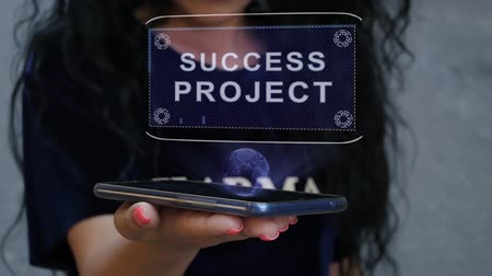 potencjał : Unrecognizable curly brunette woman showing HUD hologram with text Success project. Girl uses technology of the future on a mobile screen