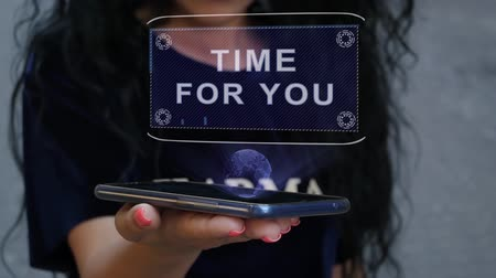 filosofie : Unrecognizable curly brunette woman showing HUD hologram with text Time for you. Girl uses technology of the future on a mobile screen