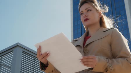 controleur : Beautiful happy woman holds in her hands paper on a background of modern buildings. A blonde with red lips looks straight and holds a contract or report