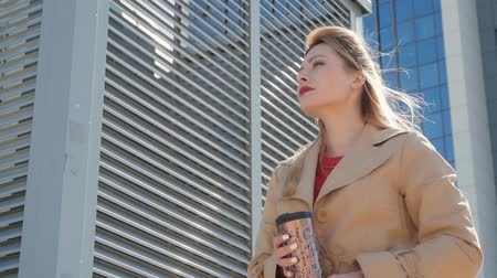 сохранять : Beautiful happy woman holds in her hands thermo mug on a background of modern buildings. A blonde with red lips looks straight and holds thermos