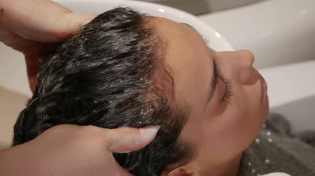 saç kremi : Hairdresser massages female hair in a beauty salon. Beautiful young woman cares for hair health, cosmetic procedures shampoo, woman in spa beauty salon