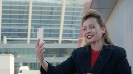 dizer : Beautiful happy woman laughing and talking. Video call on the phone against the background of modern buildings. The blonde with red lips makes live stream on the street and smiles in a conversation